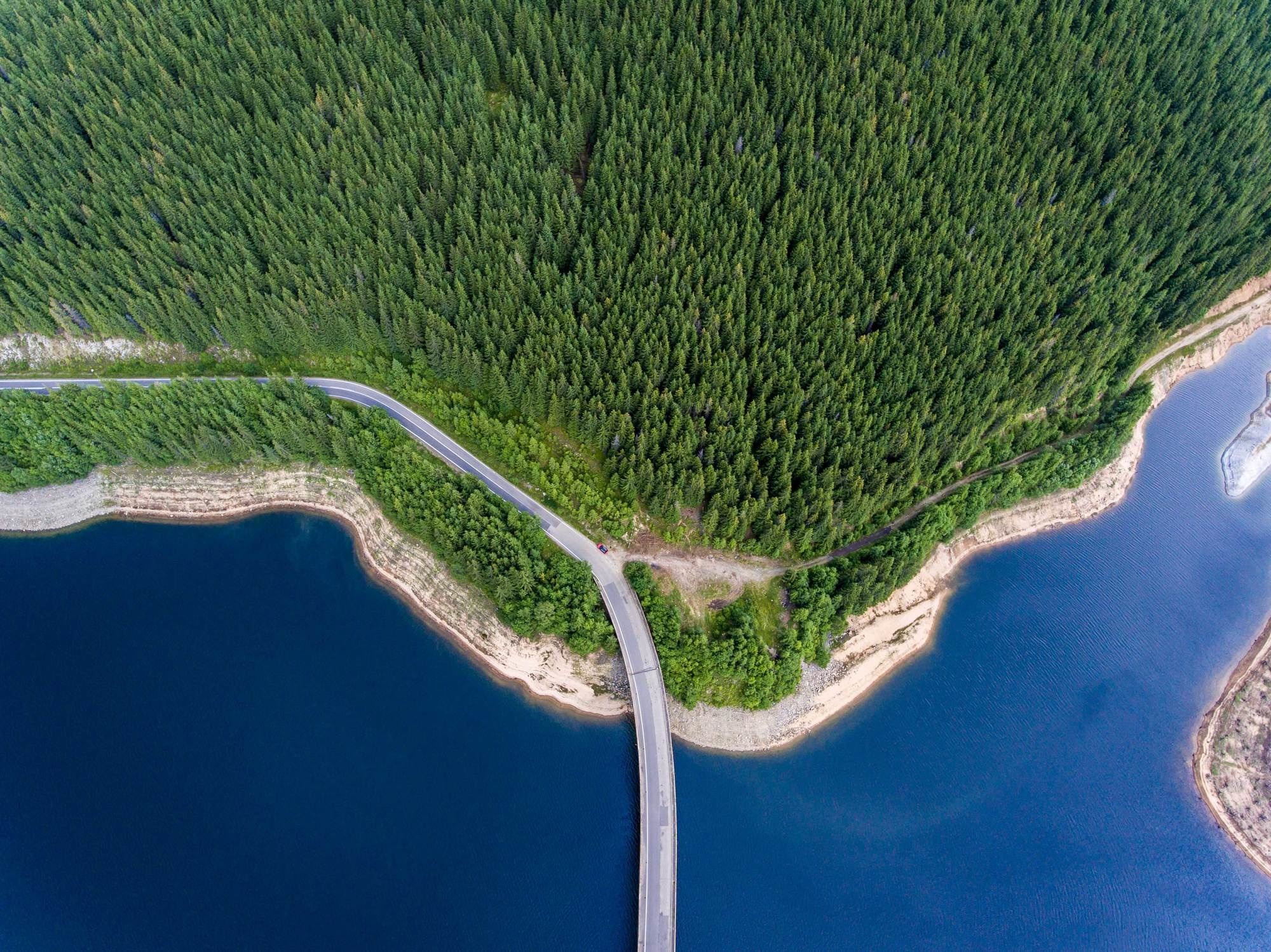 Arial view of a road bridge over a lake and mountain forest